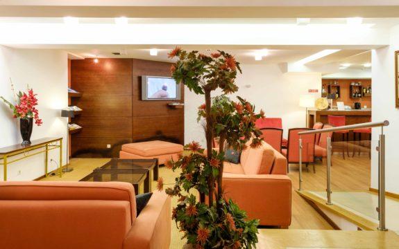Fotografia de entrada de hotel com sofás e uma planta
